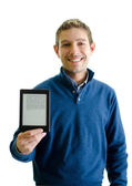 Handsome young man showing ebook reader — Stock Photo
