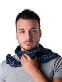 Young man with scarf, holding his neck because of throat ache — Stock Photo