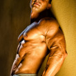 Handsome young bodybuilder against wall — Photo