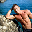 Smiling young bodybuilder leaning against sea rock — Stock Photo #27777777