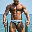 Attractive young bodybuilder getting out of sea or ocean — Stock Photo