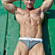 Handsome young bodybuilder leaning on wood planks, smiling — Stock Photo