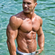 Handsome, hot young bodybuilder in the sea — Stock Photo