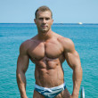 Handsome young bodybuilder standing with sea or ocean behind — Stock Photo #27778099