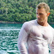 Handsome young bodybuilder by the sea with wet shirt on — Stock Photo