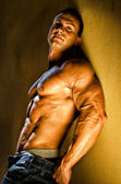 Handsome young bodybuilder against wall — Stock Photo