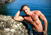 Smiling young bodybuilder leaning against sea rock — Stock Photo