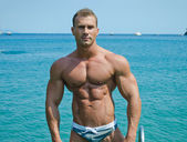 Handsome young bodybuilder standing with sea or ocean behind — Stock Photo