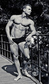 Attractive young bodybuilder smiling, outdoors, showing muscular body — Stock Photo