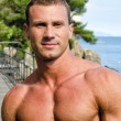 Handsome young muscle man smiling, outdoors — Stok fotoğraf