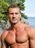 Pohledný mladý muž svalů s úsměvem, venku — Stock fotografie