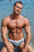 Smiling, muscular young bodybuilder shirtless on his knees — Stock Photo
