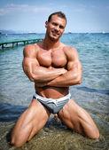 Handsome young bodybuilder in bathing suit kneeling — Stock Photo