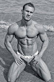 Handsome young bodybuilder in bathing suit kneeling on the beach — Stock Photo