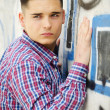 Attractive young man standing next to colorful graffiti — Stock Photo
