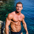 Handsome young bodybuilder shirtless by the sea or ocean — Stock Photo