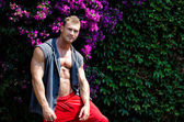 Handsome muscular young man outdoors with flowers behind — Stock Photo