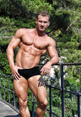 Handsome young bodybuilder shirtless outdoors in sunny day — Stock Photo