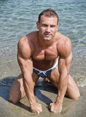 Attractive muscular young man on his knees on the beach — Stock Photo
