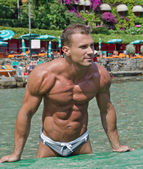 Handsome young bodybuilder on the beach — Stock Photo