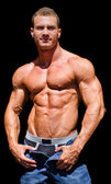 Handsome young bodybuilder shirless, isolated on black — Stock Photo