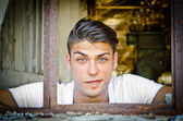Handsome young man with funny expression in rusty window — Stock Photo