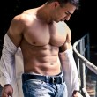 Stock Photo: Attractive bodybuilder with open shirt showing torso muscles