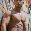 Handsome, muscular bodybuilder against graffiti wall — Foto de Stock
