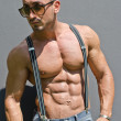Stock Photo: Handsome, muscular bodybuilder with suspenders shirtless