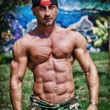 Stock Photo: Shirtless bodybuilder showing torso muscles, abs, pecs and arms outdoors