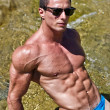 Stock Photo: Young muscle moutdoors in water showing muscular abs, pecs and arms