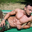 Stock Photo: Bodybuilder's naked torso, pecs, abs, leaning on bench