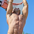 Stock Photo: Muscular mhanging from basketball ring