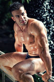 Muscular, wet bodybuilder sitting on railing — Stock Photo
