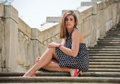 Gorgeous girl sitting on marble stairs — Stock Photo