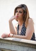 Pretty girl on marble parapet or banister — Stock Photo