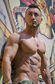 Handsome, muscular bodybuilder against graffiti wall — Stock Photo