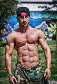 Shirtless bodybuilder showing torso muscles, abs, pecs and arms outdoors — Stock Photo