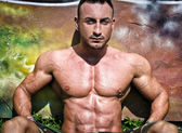 Handsome, muscular bodybuilder sitting against colorful wall — Stock Photo