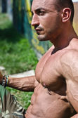 Handsome, muscular bodybuilder shirtless sitting on the grass — Stock Photo