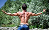 Muscle man outdoor, back shot with arms spread open — Stock Photo