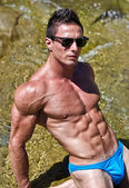 Young muscle man outdoors in water showing muscular abs, pecs and arms — Stock Photo