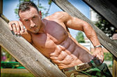 Muscular bodybuilder laying on wood stairs on a side — Stock Photo