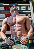 Muscular bodybuilder laying on wood stairs in the sun — Stock Photo
