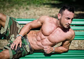 Bodybuilder's naked torso, pecs, abs, leaning on a bench — Stock Photo