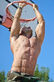 Muscular man hanging from basketball ring — Stock Photo