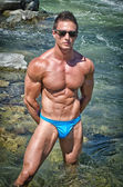 Young bodybuilder standing in river water, shirtless with sunglasses — Stock Photo