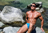 Handsome young muscle man sitting on stone by river water sunbathing with sunglasses on — Stock Photo