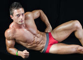 Attractive young muscle man on the floor with muscular ripped body — Stock Photo