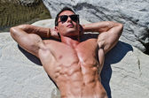 Attractive young muscle man sunbathing on rock — Stock Photo